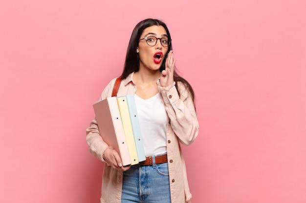 Giovane donna graziosa che si sente felice, eccitata e positiva, dando un grande grido con le mani vicino alla bocca, chiamando. concetto di studente