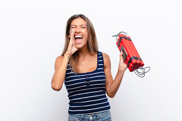 Giovane bella donna che si sente felice, eccitata e positiva, gridando con le mani vicino alla bocca, gridando con una bomba alla dinamite