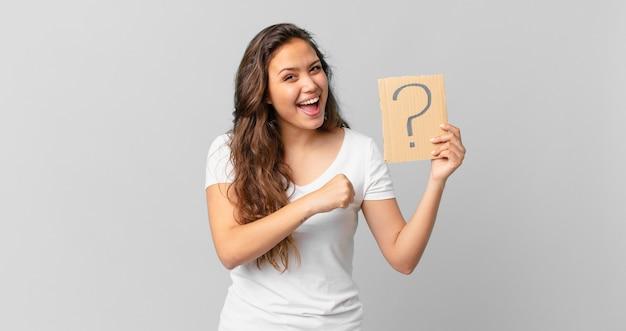 Giovane bella donna che si sente felice e affronta una sfida o celebra e tiene in mano un segno di punto interrogativo