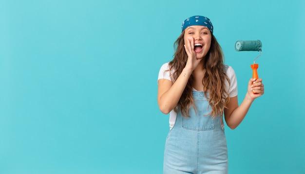Giovane bella donna che si sente felice, fa un grande grido con le mani vicino alla bocca e dipinge un muro