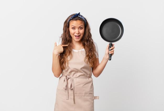 Giovane bella donna che si sente felice e indica se stessa con un concetto di chef eccitato e tiene in mano una padella