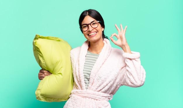 Giovane bella donna che si sente felice, rilassata e soddisfatta, mostrando approvazione con un gesto ok, sorridente. concetto di pigiama