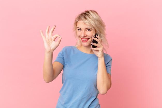 Giovane bella donna che si sente felice, mostrando approvazione con un gesto ok. concetto di cellula