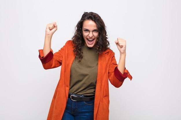 Giovane donna graziosa che si sente felice, sorpresa e orgogliosa, grida e celebra il successo con un grande sorriso contro il muro bianco
