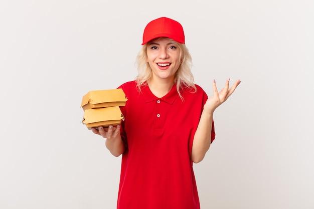 Giovane bella donna che si sente felice, sorpresa nel realizzare una soluzione o un'idea. concetto di consegna di hamburger