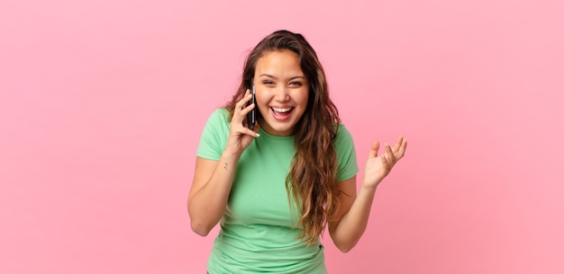 Giovane bella donna che si sente felice, sorpresa nel realizzare una soluzione o un'idea e tenere in mano uno smartphone