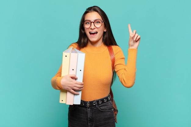 Giovane bella donna che si sente come un genio felice ed eccitato dopo aver realizzato un'idea, alzando allegramente il dito, eureka !. concetto di studente