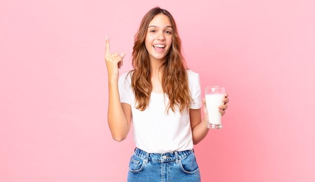 Giovane bella donna che si sente un genio felice ed eccitato dopo aver realizzato un'idea e aver tenuto in mano un bicchiere di latte