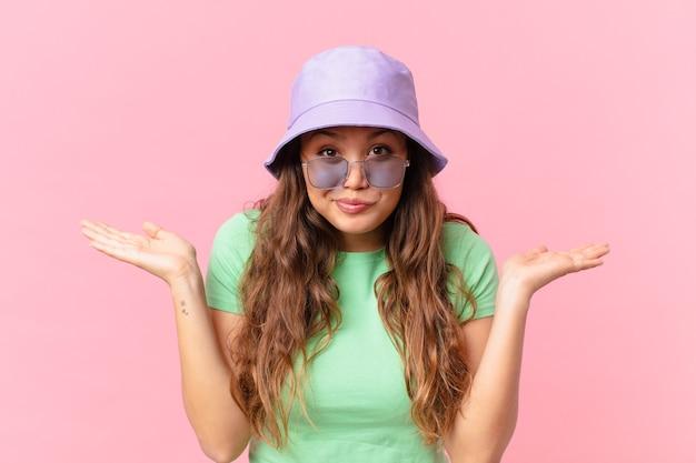 Giovane bella donna che si sente perplessa, confusa e dubbiosa. concetto di estate