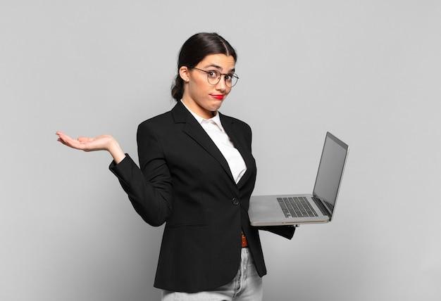 Giovane donna graziosa che si sente perplessa e confusa, dubita, appesantisce o sceglie diverse opzioni con un'espressione divertente. concetto di laptop