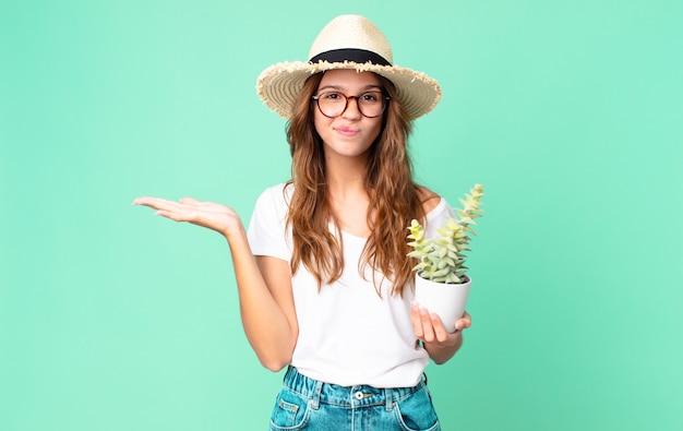 Giovane bella donna che si sente perplessa e confusa e dubita con un cappello di paglia e tiene in mano un cactus