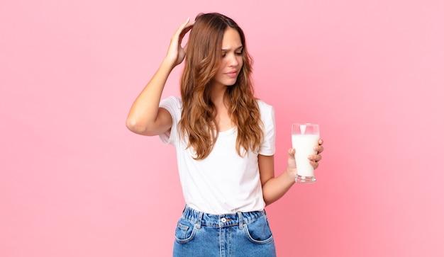 Giovane bella donna che si sente perplessa e confusa, si gratta la testa e tiene in mano un bicchiere di latte