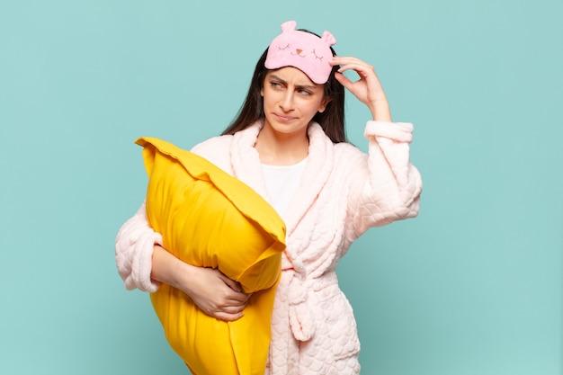 Giovane bella donna che si sente perplessa e confusa, si gratta la testa e guarda di lato. svegliarsi indossando il concetto di pigiama