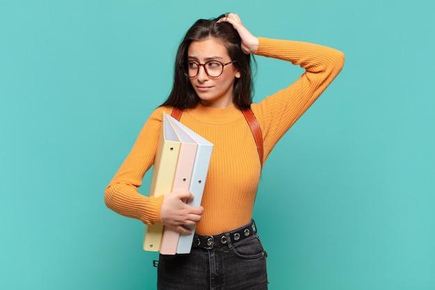 Giovane donna graziosa che si sente perplessa e confusa, grattandosi la testa e guardando di lato. concetto di studente