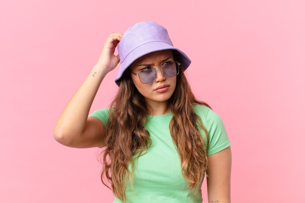 Giovane bella donna che si sente perplessa e confusa, grattandosi la testa. concetto di estate