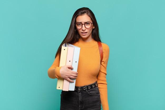 Giovane bella donna che si sente perplessa e confusa, con un'espressione stupita e sbalordita guardando qualcosa di inaspettato. concetto di studente