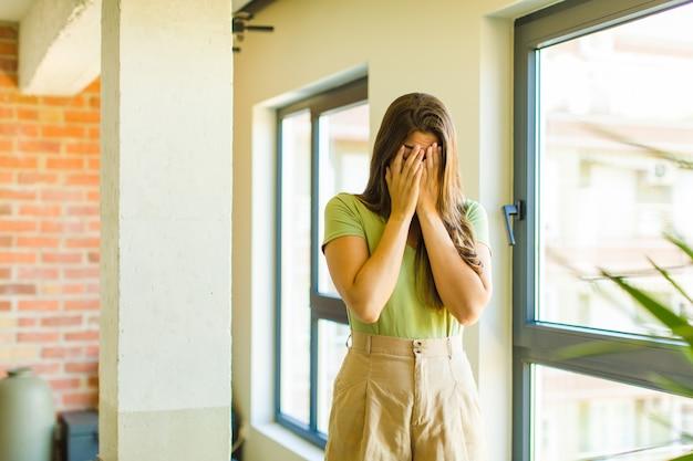 Giovane donna graziosa che si sente triste, frustrata, nervosa e depressa, che copre il viso con entrambe le mani, piangendo