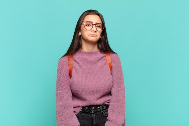 Giovane donna graziosa che si sente triste e piagnucolona con uno sguardo infelice, piange con un atteggiamento negativo e frustrato. concetto di studente