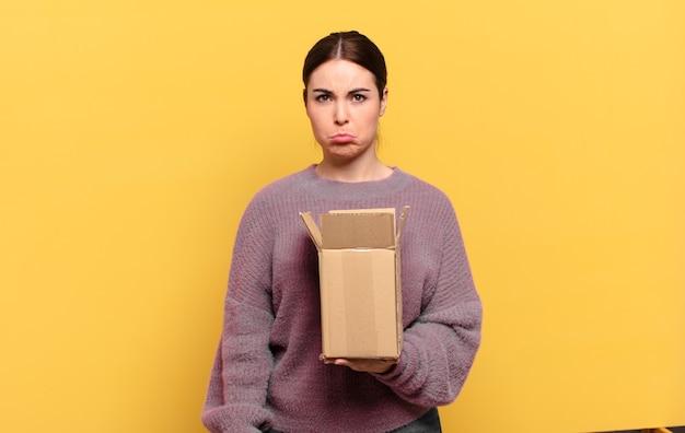 Giovane donna graziosa che si sente triste e piagnucolona con uno sguardo infelice, piange con un atteggiamento negativo e frustrato