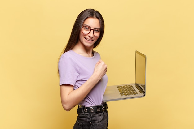Giovane bella donna che si sente scioccata, eccitata e felice, ridendo e celebrando il successo, dicendo wow!. concetto di laptop