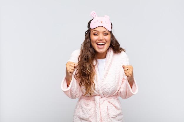 Giovane bella donna che si sente scioccata, eccitata e felice, ride e celebra il successo, dicendo wow! indossa il pigiama