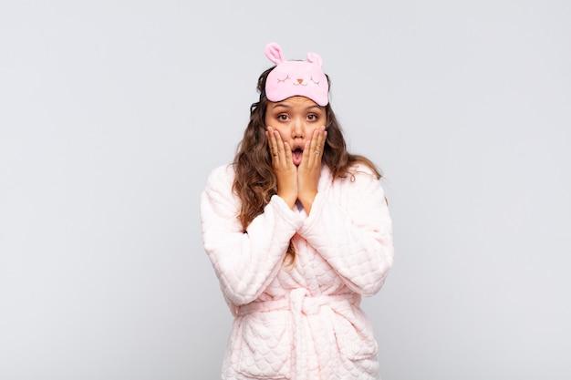 Giovane donna graziosa che si sente scioccata e spaventata, sembra terrorizzata con la bocca aperta e le mani sulle guance che indossano il pigiama