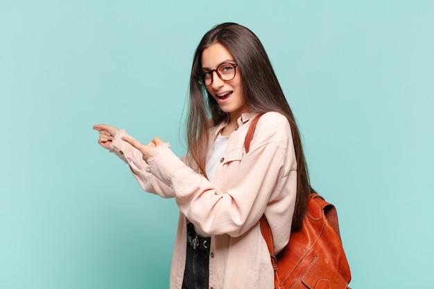 Giovane donna graziosa che si sente scioccata e sorpresa, indicando lo spazio di copia sul lato con sguardo stupito e a bocca aperta. concetto di studente