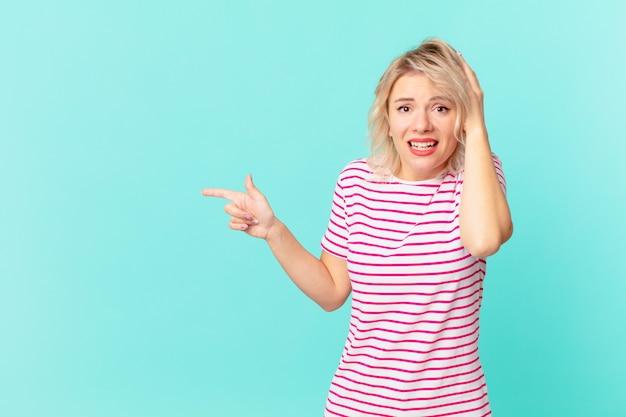 Giovane bella donna che si sente stressata, ansiosa o spaventata, con le mani sulla testa
