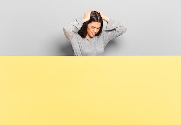 Giovane bella donna che si sente stressata e frustrata, alza le mani alla testa, si sente stanca, infelice e con emicrania. copia spazio per posizionare il tuo concetto