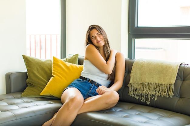 Giovane donna graziosa che si sente stanca, stressata, ansiosa, frustrata e depressa, soffre di dolore alla schiena o al collo