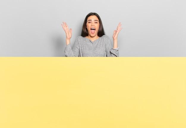 Giovane bella donna che urla furiosamente, sentendosi stressata e infastidita con le mani in alto che dice perché io. copia spazio per inserire il tuo concetto