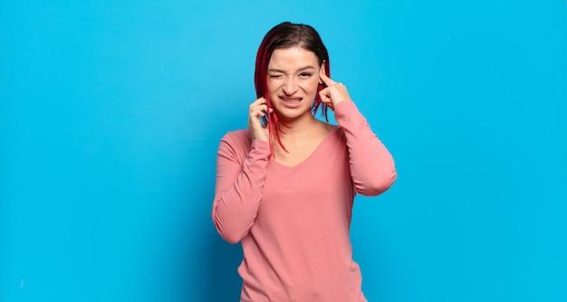 Giovane donna graziosa che gesturing sulla parete colorata