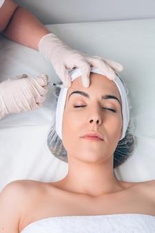 Giovane bella donna che riceve un'iniezione cosmetica in faccia come una parte del trattamento clinico. medicina, sanità e concetto di bellezza.