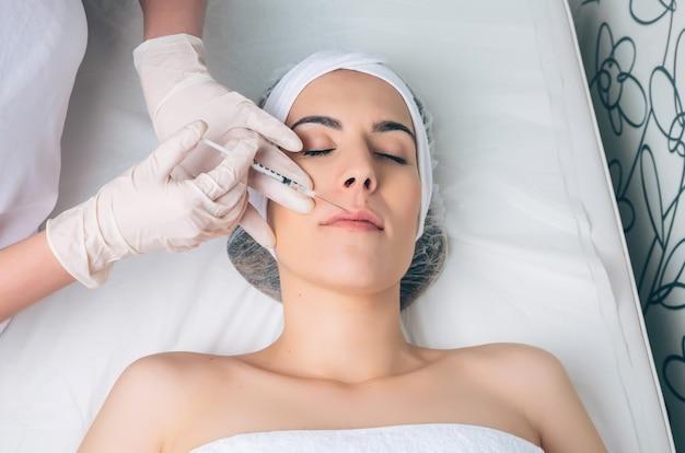 Giovane bella donna che si fa un'iniezione cosmetica in faccia come una parte del trattamento clinico. medicina, sanità e concetto di bellezza.