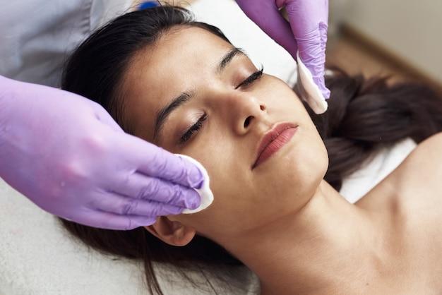 Giovane donna graziosa che ottiene trattamenti nei saloni di bellezza. pulizia della pelle con dischetti di cotone