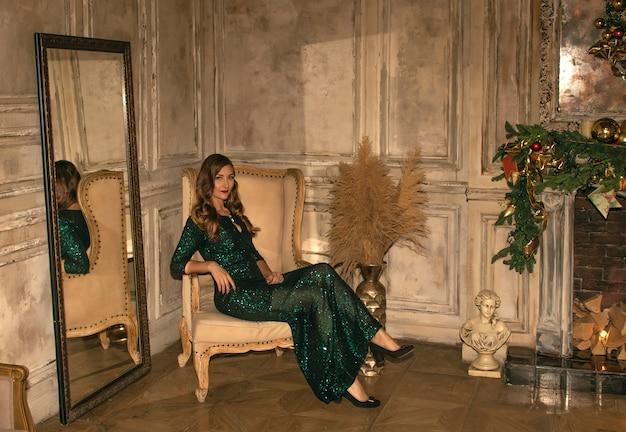 Giovane donna graziosa in primo piano del vestito scintillato verde con le decorazioni di natale