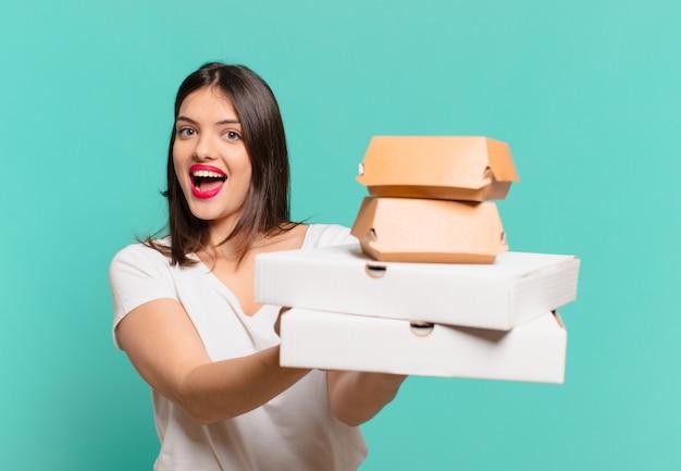 Giovane bella donna felice espressione e tenendo pizze da asporto