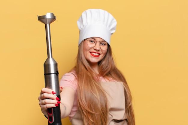 Giovane donna graziosa. concetto di chef di espressione felice e sorpreso