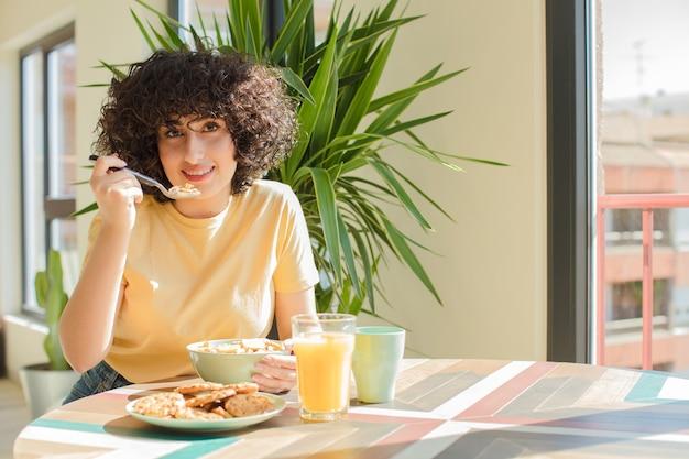 Giovane e bella donna facendo colazione a casa.