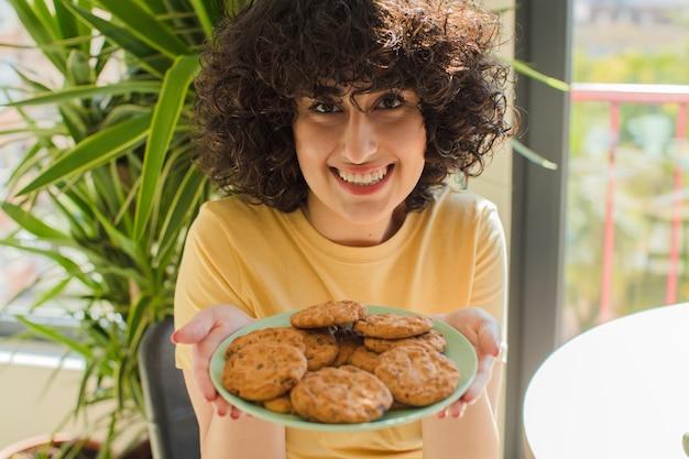 Giovane donna graziosa che mangia colazione a casa