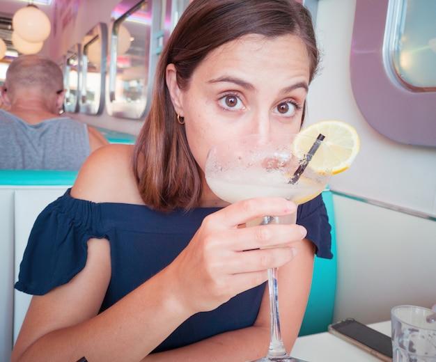 Giovane donna graziosa che ha un cocktail mojito fresco in un ristorante