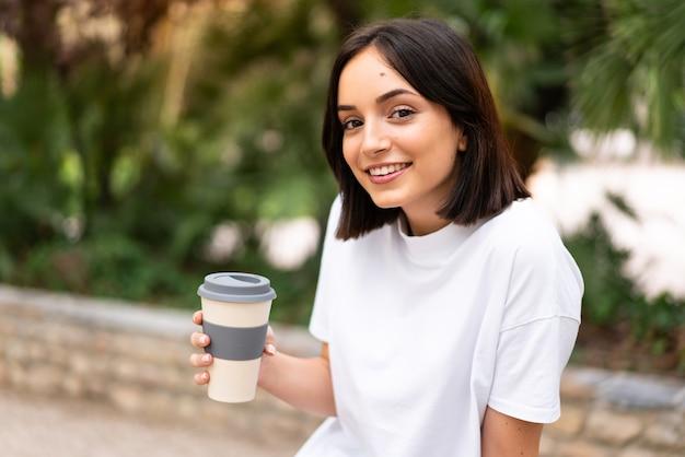 Giovane donna graziosa che tiene il caffè da portare via all'aperto