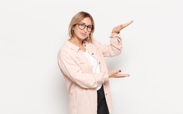 Giovane donna graziosa che tiene un oggetto con entrambe le mani sullo spazio della copia laterale, mostrando, offrendo o pubblicizzando un oggetto