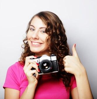 Giovane donna graziosa che tiene macchina fotografica d'epoca su sfondo grigio.