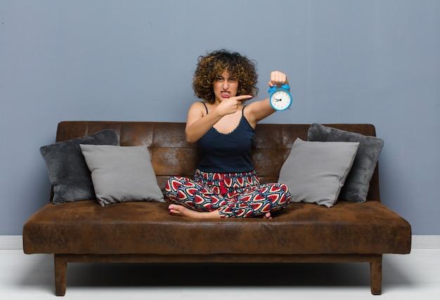 Giovane donna graziosa a casa seduto su un divano con un orologio