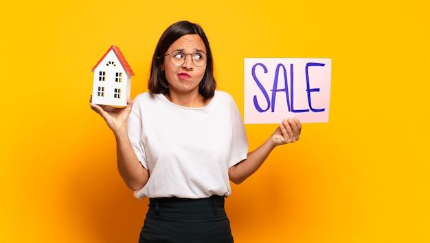 Giovane casa graziosa della donna per il concetto di vendita