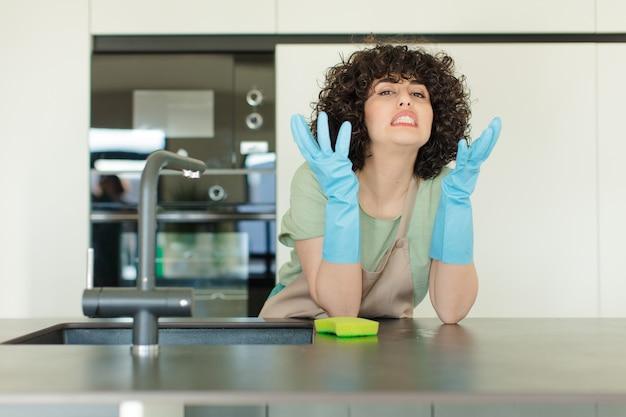Governante della giovane donna graziosa che lava i piatti a casa