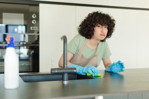 Giovane donna graziosa governante lavare i piatti a casa