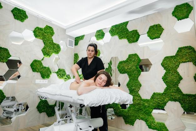 Una giovane donna graziosa sta godendo di un massaggio cosmetologico professionale presso la spa