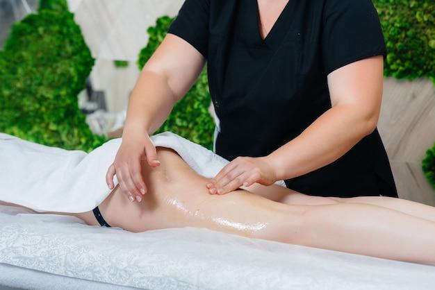 Una giovane donna graziosa sta godendo di un massaggio professionale con miele presso la spa